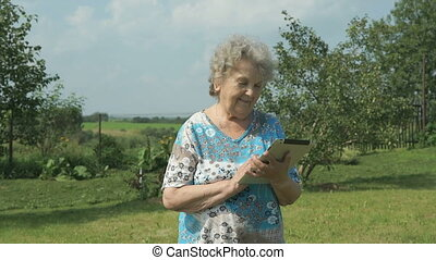 Elderly woman walking with digital tablet outdoors