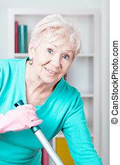 Elderly woman washing floor