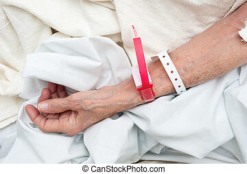 Elderly woman wearing medical arm bands - An elderly woman...
