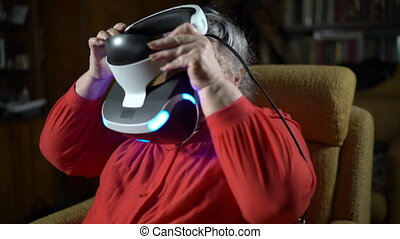 Elderly woman wearing VR headset in front of TV screen