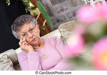 elderly woman wiping her tears