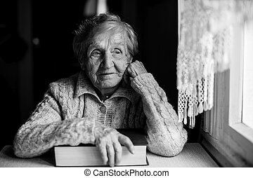 Elderly woman with a book near the window.