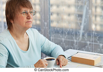 Elderly woman with a cup of coffee