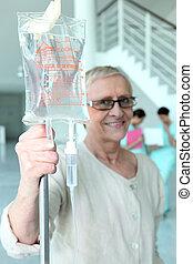Elderly woman with a hospital drip