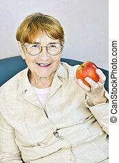 Elderly woman with apple