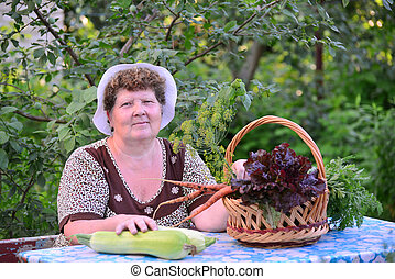 elderly woman with basket of vegetables sitting at the table...