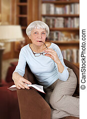 elderly woman with book and glasses sitting in a chair, mother, grandmother