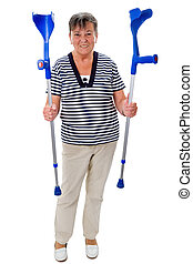 Elderly woman with crutches