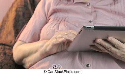 Elderly woman with digital tablet computer indoors