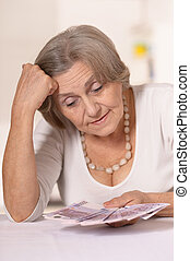 Elderly woman with euros