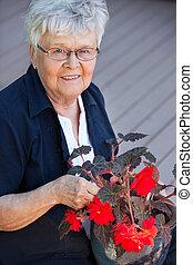 Elderly woman with flower pot