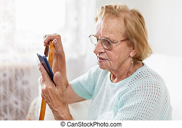 Elderly woman with glasses using a mobile phone