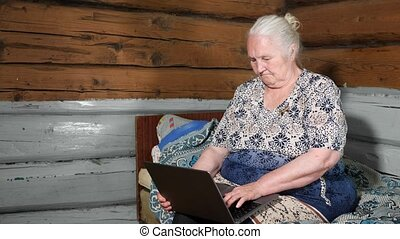 elderly woman with gray hair holds a laptop on her lap ...