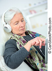 elderly woman with headset connected to a tablet