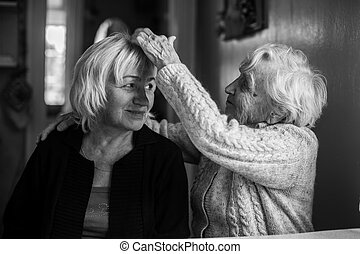 Elderly woman with her adult daughter. Black and white photo.