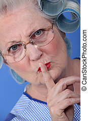 Elderly woman with her hair in rollers holding her finger up to her lips