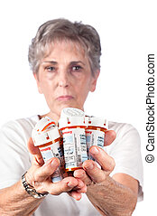 A senior adult woman shows the many medications she must take to remain healthy. Note to reviewer: Most of the barcoding on the two right bottle has been removed and a good portion of the left bottle top part of the barcode was removed. The remaining bars have been greatly changed to simply ...