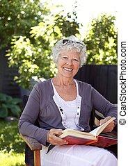 Elderly woman with novel in garden