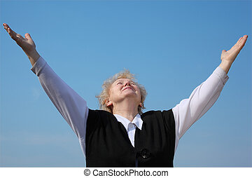 Elderly woman with rised hands looks in sky