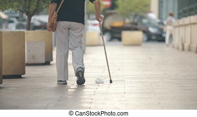 Elderly woman with stick walking in the street - Back view...