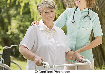Elderly woman with the nurse helping her - Elderly woman...
