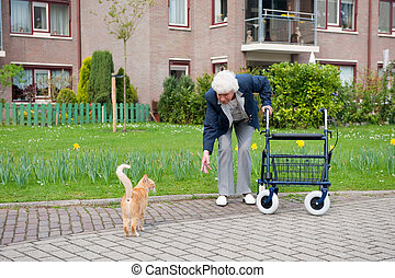 Elderly woman with walker and cat