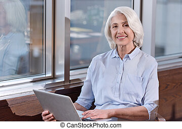 Elderly woman working on laptop in an office - Full of...