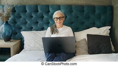 Elderly Woman Working on Laptop - Senior female in...