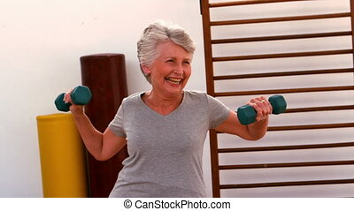 Elderly woman working out with dumbbells in slow motion