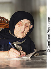 Elderly woman writing at table
