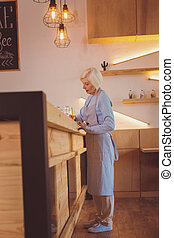 Elderly woman writing while standing behind bar counter