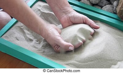 Elderly woman's hands digging in the sand in a box. Rehabilitation after an illness, psychological relief. High quality FullHD footage