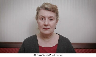 Elderly women and feelings, portrait of serious senior caucasian woman with severe look staring at camera.