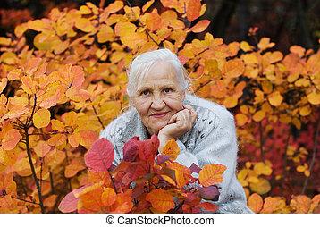 Elderly women at the autumn backgro