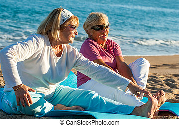 Elderly women doing stretching exercises on beach.