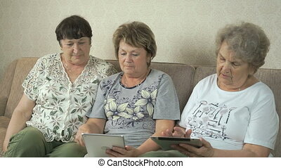 Elderly women look at photos using digital tablets
