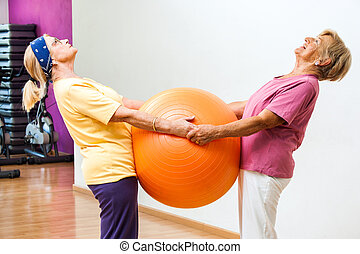 Elderly women stretching with gym ball.