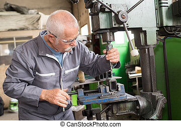 elderly worker watches processing of detail on milling...