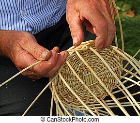 Elder's hands working the cane to make a wicker basket