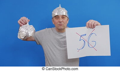 Eldery Man holding placard with no 5g sign. protesting against 5G technology and 5G-compatible antenna deployment while standing at blue background