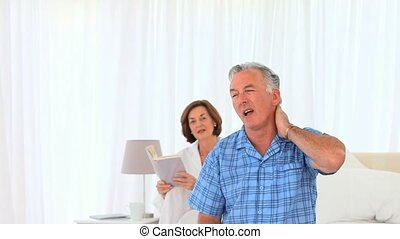 Eldery woman massaging her husbands neck