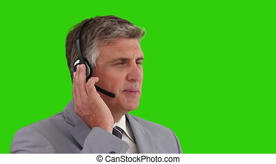 Eldlery man in  a gray suit speaking over the headset