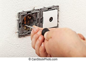 Electician hands installing electical wall sockets - closeup, focus on the fixture