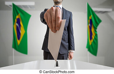 Election or referendum in Brazil. Voter holds envelope in...