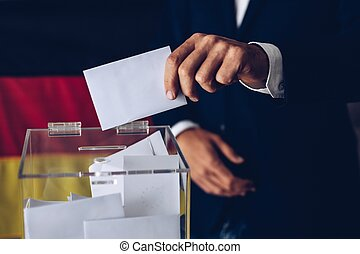 Elections in Germany. Man throwing his vote into the ballot box.