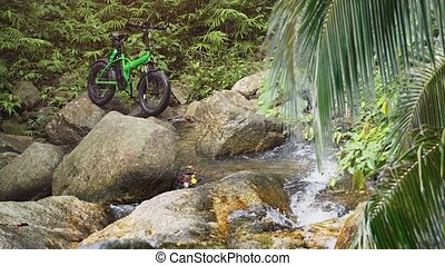 Electric Bicycle Parked on Rocks over Tropical Mountain Stream