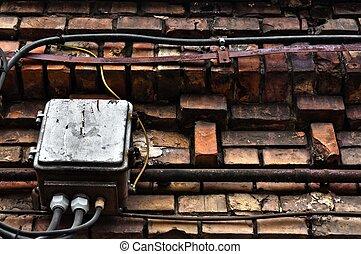 Electric box on abandoned brick wall