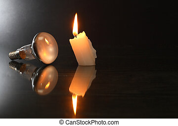 Electric Bulb Against Candle - Blackout concept. One ...