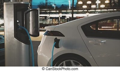 Electric Car Charging At A Charging Station (evening...