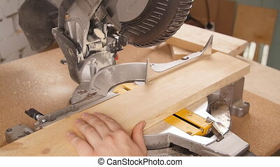 Electric circular saw cutting piece of wood in sawmill